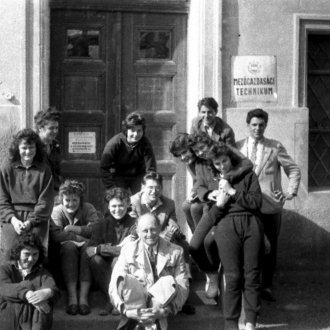 Tanár és diákjai az iskola bejáratánál